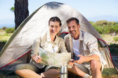 Couple looking at the map outside tent — Stock Photo
