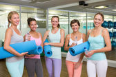 Smiling women in fitness studio before yoga class — Stockfoto