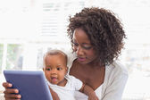 Happy mother using tablet pc with baby boy — Stockfoto