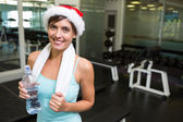 Fit brunette in santa hat smiling at camera — Stockfoto