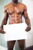 Muscular man holding blank board — Stock Photo