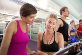Trainer talking to her client on the treadmill — Stock Photo