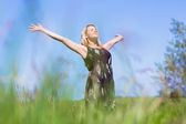 Pretty blonde in sundress standing with arms out — Stock Photo