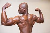 Shirtless young muscular man flexing muscles — Stock Photo
