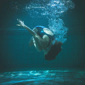 Athletic swimmer doing a somersault underwater — Stock Photo
