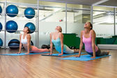Yoga class in cobra pose in fitness studio — Stock Photo