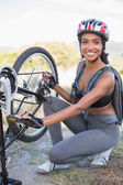 Fit woman fixing the chain on her bike — Stock Photo