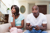 Woman sitting next to her boyfriend playing video games — Foto Stock