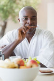 Happy man in bathrobe having breakfast on terrace — Stock Photo