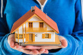 Hands holding miniature house model — Stockfoto