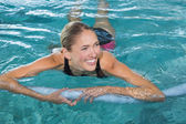 Blonde swimming with foam roller — Стоковое фото