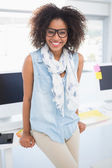 Pretty designer smiling at camera leaning on desk — Stock Photo
