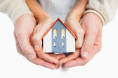 Couple holding small model house in hands — Stock Photo
