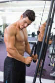 Shirtless muscular man using triceps pull down in gym — 图库照片
