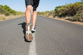 Fit man jogging on the open road  — Stockfoto