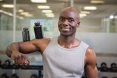 Body builder holding bottles with supplements on biceps — Stock Photo