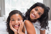 Smiling mother and daughter posing together on bed — Stock Photo