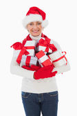 Festive woman smiling at camera holding gifts — Foto Stock