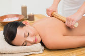 Beautiful brunette enjoying a bamboo roller massage — Stock Photo