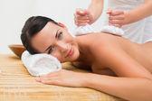 Beautiful brunette enjoying a herbal compress massage smiling at — Stock Photo