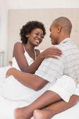 Happy couple sitting on bed cuddling — Stock Photo