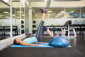 Fit brunette using bosu ball to work out — Foto de Stock