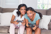 Happy mother and daughter playing video games — Stock Photo
