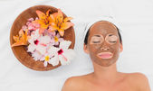 Smiling brunette getting a mud treatment facial beside bowl of f — Stock Photo