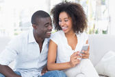 Attractive couple sitting on couch together looking at smartphon — Stockfoto