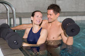 Happy couple working out with foam dumbbells — Stock Photo