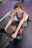 Fit smiling brunette working out on rowing machine — Stock Photo