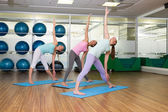 Yoga class in extended traingle position in fitness studio — Stock Photo