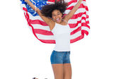 Pretty girl wrapped in american flag jumping — Stock fotografie