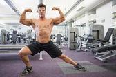 Shirtless muscular man flexing muscles in gym — Stok fotoğraf
