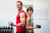Fit couple lifting dumbbells together smiling at camera — ストック写真