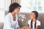 Pretty mother with her daughter offering flowers — Stock Photo