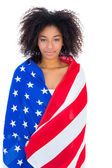 Pretty girl wrapped in american flag smiling at camera — ストック写真