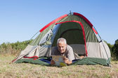 Happy camper looking at map lying in his tent — Stock Photo
