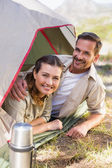 Outdoorsy couple smiling at camera from inside their tent — Stock fotografie