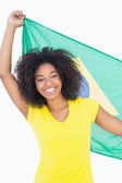 Pretty girl in yellow tshirt holding brazilian flag smiling at c — Stock Photo