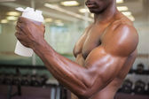 Sporty man holding protein drink in gym — Stock Photo