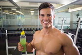 Sporty young man with energy drink in gym — Stock Photo
