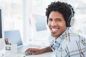 Young designer listening to music as he works — Stock Photo