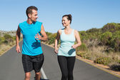 Fit happy couple jogging on the open road together — Stock Photo