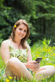 Relaxed woman text messaging in field — 图库照片
