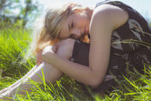 Pretty blonde in sundress sitting on grass — Foto Stock