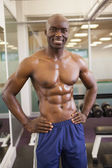 Smiling shirtless muscular man with hands on hips — Stock Photo