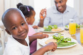 Family enjoying a healthy meal together with son smiling at came — Stock Photo