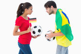 German and brazilian football fan facing off — Stock Photo