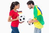 German and brazilian football fan facing off — Stockfoto